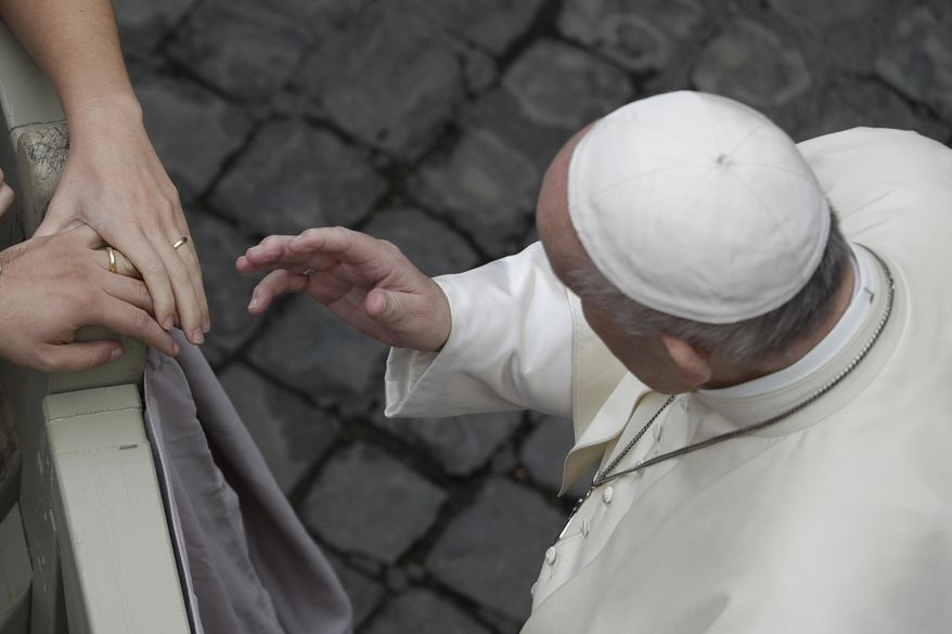 Pope Francis blesses a newly wed couple during his weekly general audience in the St. Damaso courtyard at the Vatican, Wednesday, Sept. 30, 2020. (AP Photo/Gregorio Borgia)