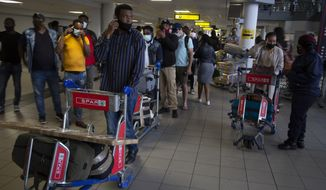 Passengers queue to access the O.R. Tambo Airport in Johannesburg, Thursday Oct. 1, 2020. South Africa has reopened to international flights, ending a six-month ban on international travel that was part of its restrictions to combat the spread of COVID-19. (AP Photo/Denis Farrell)