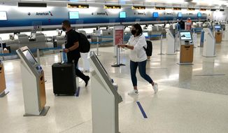 Passengers walk through a largely empty check-in area for American Airlines at Miami International Airport during the coronavirus pandemic, Wednesday, Sept. 30, 2020, in Miami. The airline industry has been decimated by the pandemic. The Payroll Support Program given to the airlines as part of the CARES Act runs out Thursday. (AP Photo/Lynne Sladky)