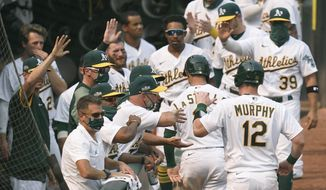 Oakland Athletics' Sean Murphy (12) and Tommy La Stella, second from lower right, are congratulated by teammates after both scored against the Chicago White Sox during the fifth inning of Game 3 of an American League wild-card baseball series Thursday, Oct. 1, 2020, in Oakland, Calif. (AP Photo/Eric Risberg)