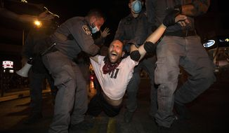 Israeli police officers detain an Israeli protester during a demonstration against lockdown measures that they believe are aimed at curbing protests against prime minister Benjamin Netanyahu in Tel Aviv, Israel, Thursday, Oct. 1, 2020. (AP Photo/Sebastian Scheiner)