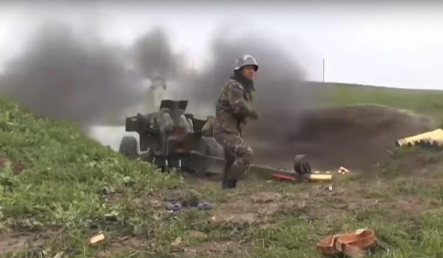 This image taken from a video released by Armenian Defense Ministry on Friday, Oct. 2, 2020 an Armenian serviceman fires a cannon towards Azerbaijan positions at the contact line of the self-proclaimed Republic of Nagorno-Karabakh, Azerbaijan. Clashes broke out Sunday in Nagorno-Karabakh, a region within Azerbaijan that has been controlled by ethnic Armenian forces backed by the Armenian government since the end of a separatist war a quarter-century ago. (Armenian Defense Ministry via AP)