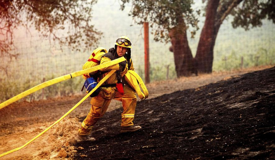 A firefighter battles the Glass Fire burning in a Calistoga, Calif., vineyard Thursday, Oct. 1, 2020. (AP Photo/Noah Berger)