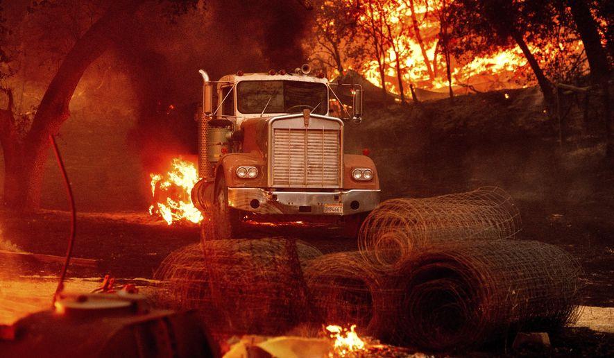 Flames from the Glass Fire burn a truck in a Calistoga, Calif., vineyard Thursday, Oct. 1, 2020. (AP Photo/Noah Berger)