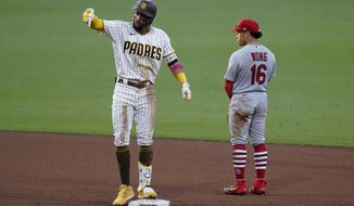 San Diego Padres' Fernando Tatis Jr., left, reacts after hitting a double, next to St. Louis Cardinals second baseman Kolten Wong during the fifth inning of Game 3 of a National League wild-card baseball series Friday, Oct. 2, 2020, in San Diego. (AP Photo/Gregory Bull)
