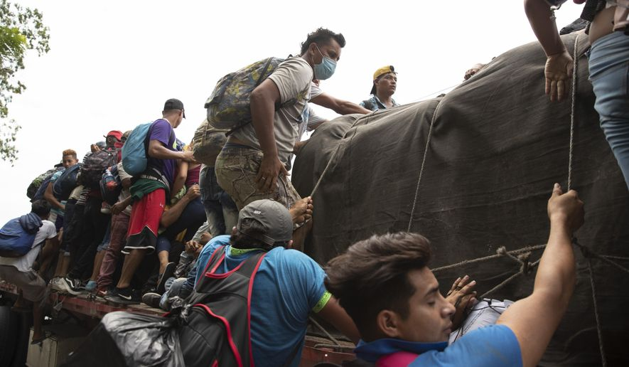 Migrants climb on to the back of a freight truck that slowed down to give them an opportunity to jump on in Rio Dulce, Guatemala, Friday, Oct. 2, 2020. A new caravan of about 2,000 migrants set out from neighboring Honduras in hopes of reaching the United States. (AP Photo/Moises Castillo) **FILE**