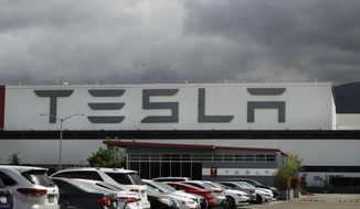 FILE - This May 12, 2020 file photo photo shows the Tesla plant in Fremont, Calif.  Tesla's third-quarter sales rose 44% from a year ago as global demand for its electric vehicles proved stronger than most other automakers. The company said it delivered 139,000 SUVs and sedans from July through September compared with 97,000 deliveries during the same period a year ago. (AP Photo/Ben Margot, File)