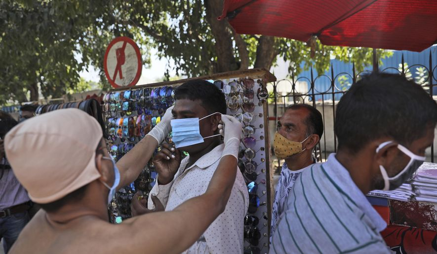 A boy dressed as Mahatma Gandhi puts a face mask on a roadside vendor during a COVID-19 awareness campaign on the birth anniversary of the independence leader, in New Delhi, India, Friday, Oct. 2, 2020. (AP Photo/Manish Swarup)