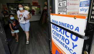 A woman leaves a store offering services to send remittances to Mexico and Central America, Friday, Sept. 11, 2020, in San Diego. Mexican workers have confounded economists by sending home huge amounts of money during the coronavirus pandemic. Experts had predicted that migrant workers would wire less money, known as remittances, as the American economy took a dive. (AP Photo/Gregory Bull)