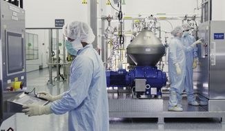 In this undated image from video provided by Regeneron Pharmaceuticals on Friday, Oct. 2, 2020, scientists work with a bioreactor at a company facility in New York state, for efforts on an experimental coronavirus antibody drug. Antibodies are proteins the body makes when an infection occurs; they attach to a virus and help the immune system eliminate it. (Regeneron via AP)