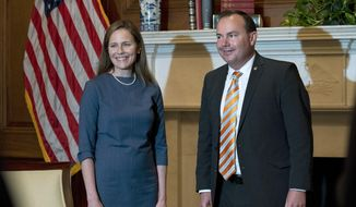 In this Sept. 29, 2020, photo, Judge Amy Coney Barrett, President Donald Trump's nominee to the Supreme Court, both without masks, poses with Sen. Mike Lee, R-Utah, at the Capitol in Washington. Hours after President Donald Trump announced he had tested positive for the coronavirus, Republican Utah Sen. Mike Lee revealed he too had been infected with the disease. (Stefani Reynolds/Pool via AP, File)