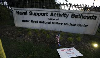 A sign and a flag are left at the main gate of Walter Reed National Military Medical Center in Bethesda, Md., Saturday Oct. 3, 2020. Stricken by COVID-19, Trump was flown to Walter Reed on Friday night. (AP Photo/Jose Luis Magana)