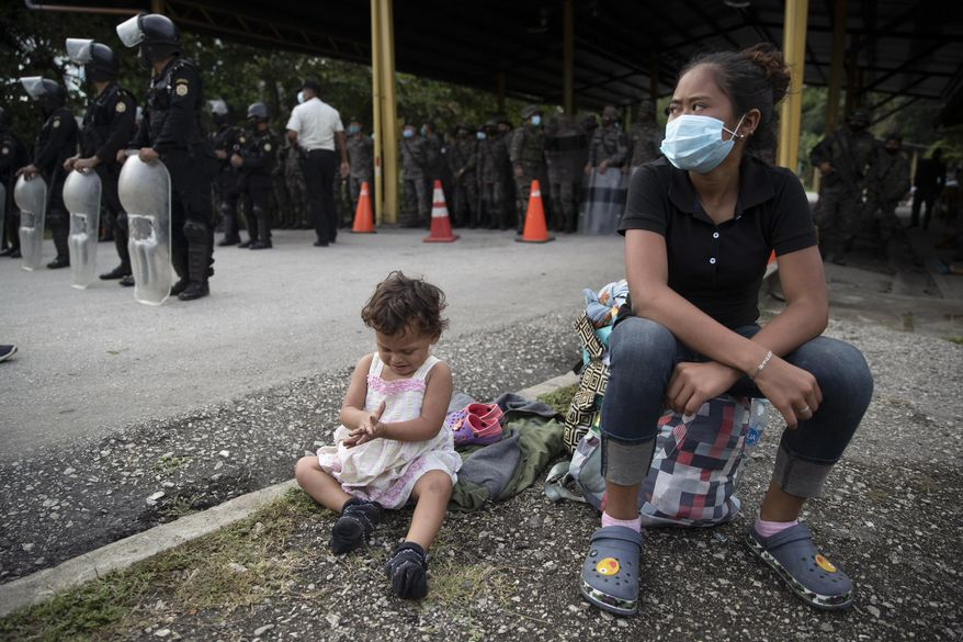 An Honduran migrant and her daughter sit at a roadblock set by security forces in Poptun, Guatemala, Friday, Oct. 2, 2020. Guatemala vowed to detain and return members of a new caravan of hundreds of migrants that set out from neighboring Honduras in hopes of reaching the United States, saying they represent a health threat amid the coronavirus pandemic. (AP Photo/Moises Castillo)