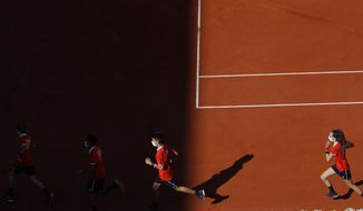 Ball girls and boys run as they get switched in the third round match of the French Open tennis tournament between Germany's Daniel Altmaier and Italy's Matteo Berrettini at the Roland Garros stadium in Paris, France, Saturday, Oct. 3, 2020. (AP Photo/Christophe Ena)