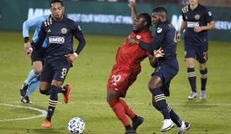 """Toronto FC's Ayo Akinola, center, is pressured by Philadelphia Union's Jose """"El Brujo"""" Martinez, left, and Mark McKenzie, front right, during the second half of an MLS soccer match, Saturday, Oct. 3, 2020, in East Hartford, Conn. (AP Photo/Jessica Hill)"""