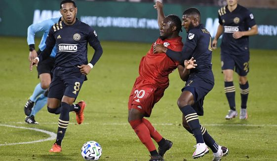 "Toronto FC's Ayo Akinola, center, is pressured by Philadelphia Union's Jose ""El Brujo"" Martinez, left, and Mark McKenzie, front right, during the second half of an MLS soccer match, Saturday, Oct. 3, 2020, in East Hartford, Conn. (AP Photo/Jessica Hill)"
