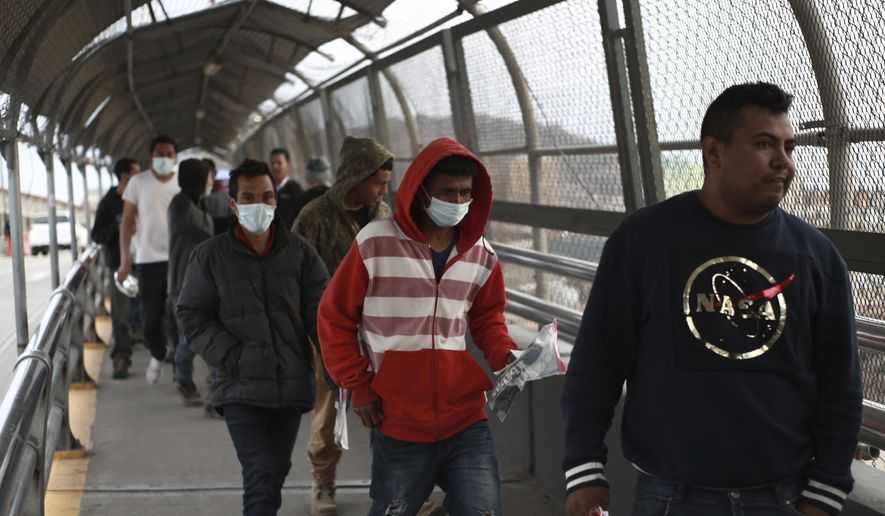 In this March 21, 2020, photo, Central American migrants seeking asylum, some wearing protective face masks, return to Mexico via the international bridge at the U.S-Mexico border that joins Ciudad Juarez and El Paso. (AP Photo/Christian Chavez) **FILE**