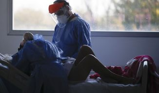 A heath worker attends a patient in an intensive care unit designated for people infected with COVID-19 at a hospital in Buenos Aires, Argentina, Friday, Oct. 2, 2020. (AP Photo/Natacha Pisarenko)
