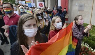 """People hold a protest rally in front of Poland's Education Ministry in Warsaw, Poland, Sunday, Oct. 4, 2020, against the appointment of a new education minister Przemyslaw Czarnek. Czarnek has said that LGBT people """"are not equal to normal people."""" LGBT rights are the focus of a growing culture clash in Poland. (AP Photo/Czarek Sokolowski)"""