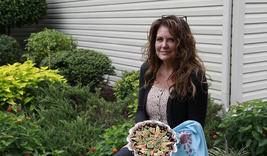 Karen Freidt smiles as she holds her blueberry pie outside her home in Newport News, Va., Monday, Sept. 21, 2020. Freidt's pies, which she began baking during quarantine, garnered national recognition when a top fashion designer, Anna Sui who was pulling together her Spring 2021 collection, requested to use one during a virtual show. (Kaitlin McKeown/The Virginian-Pilot via AP)