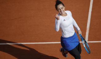 Italy's Martina Trevisan clenches her fist after scoring a point against Netherlands' Kiki Bertens in the fourth round match of the French Open tennis tournament at the Roland Garros stadium in Paris, France, Sunday, Oct. 4, 2020. (AP Photo/Christophe Ena)