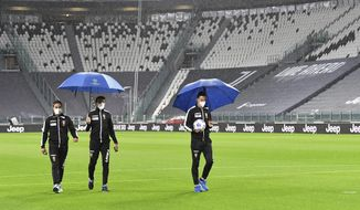 Referee Daniele Doveri, right, flanked by assistants Filippo Meli and Daniele Bindoni inspects the pitch of the Allianz Stadium in Turin, Italy, Sunday, Oct. 4, 2020 ahead of the scheduled Serie A soccer match between Juventus and Napoli. Napoli is likely to be handed a 3-0 loss by the Italian league's judge for failing to show for its Serie A match at Juventus on Sunday night. Napoli did not travel to Turin for the match after local health authorities ordered the squad into quarantine after two players tested positive for the coronavirus. (Tano Pecoraro/LaPresse via AP)