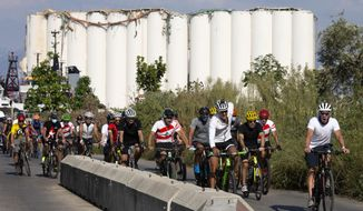 """Former American professional cyclist Lance Armstrong, right, rides with Lebanese and foreign cyclists at the site of the Aug. 4 deadly blast in the port of Beirut that killed scores and wounded thousands in Beirut, Lebanon, Sunday, Oct. 4, 2020. Armstrong led the charity bike tour named, """"Bike for Beirut,"""" to raise awareness and fund organizations that are helping residents of the Lebanese capital who suffered losses as a result of the massive blast. (AP Photo/Hassan Ammar)"""