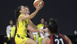 Seattle Storm guard Sue Bird (10) goes up to shoot between Las Vegas Aces center Carolyn Swords, rear, and guard Kayla McBride (21) during the second half of Game 2 of basketball's WNBA Finals, Sunday, Oct. 4, 2020, in Bradenton, Fla. (AP Photo/Phelan M. Ebenhack)