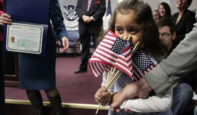 Victoria Dallas Fischer, 4, a child adopted from Guatemala, partially hides her face behind a handful of mini American flags as she goes to receive her citizenship certificate during the U.S. Citizenship and Immigration Services (USCIS) first ever Adoption Day ceremony on Thursday, Nov. 18, 2010, in New York.  In recognition of November as National Adoption Month, USCIS naturalized 17 adopted children from six countries; China, Ethiopia, Guatemala, Haiti, Saint Lucia, and South Korea, so that they may celebrate their first Thanksgiving with their families as American citizens.  (AP Photo/Bebeto Matthews)