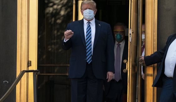 President Donald Trump walks out of Walter Reed National Military Medical Center after receiving treatment as a covid-19 patient, Monday, Oct. 5, 2020, in Bethesda, Md. (AP Photo/Evan Vucci)