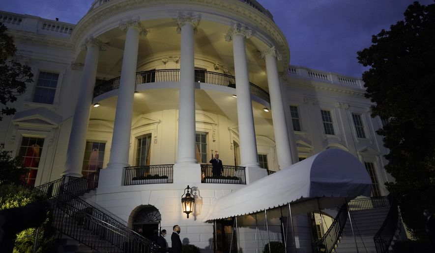 President Donald Trump salutes from the Blue Room Balcony as he returns to the White House Monday, Oct. 5, 2020, in Washington, after leaving Walter Reed National Military Medical Center, in Bethesda, Md. Trump announced he tested positive for COVID-19 on Oct. 2. (AP Photo/Alex Brandon)