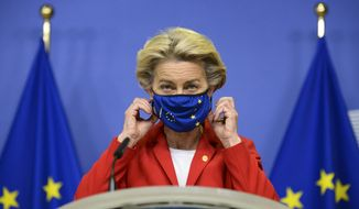 FILE - In this Thursday, Oct. 1, 2020 file photo, European Commission President Ursula von der Leyen, takes off her protective mask prior to making a statement regarding the Withdrawal Agreement at EU headquarters in Brussels. European Commission president Ursula von der Leyen says she has placed herself in isolation after being in contact with a person infected with the coronavirus. (Johanna Geron, Pool via AP)