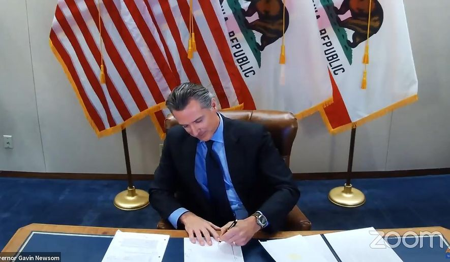 FILE - In this Wednesday, Sept. 30, 2020 file image made from video from the Office of the Governor, California Gov. Gavin Newsom signs into law a bill that establishes a task force to come up with recommendations on how to give reparations to Black Americans in Sacramento, Calif. A conservative legal group announced Monday, Oct. 5 that it sued to block California's first-in-the-nation law that requires hundreds of corporations based in the state to have directors from racial or sexual minorities on their boards. (Office of the Governor via AP, File)