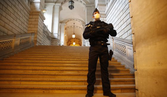 A riot police officer guards the stairs leading to the court before the trial of a 29-year-old Algerian man accused of killing a woman and trying to blow up a church near Paris, a failed 2015 attack that investigators say was orchestrated by Islamic State extremists in Syria, Monday, Oct. 5, 2020 in Paris. Instead of bombing a Sunday Mass in the Paris suburb of Villejuif, Sidi Ahmed Ghlam shot himself in the leg, and was soon arrested. (AP Photo/Francois Mori)