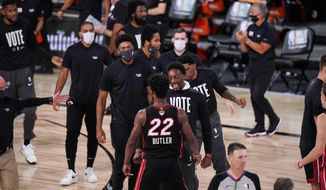 Miami Heat's Bam Adebayo, center, congratulates Miami Heat's Jimmy Butler (22) after a win against the Los Angeles Lakers 115-104 during the second half in Game 3 of basketball's NBA Finals, Sunday, Oct. 4, 2020, in Lake Buena Vista, Fla. (AP Photo/Mark J. Terrill)