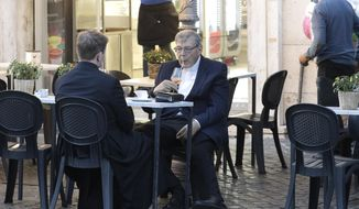 Cardinal George Pell has a drink in a cafe at the Vatican, Sunday, Oct. 4, 2020. Cardinal George Pell, who left the Vatican in 2017 to face child sexual abuse charges in Australia, returned to Rome on Wednesday to find a Holy See mired in the type of corruption scandal he worked to expose and clean up. (AP Photo/Gregorio Borgia)