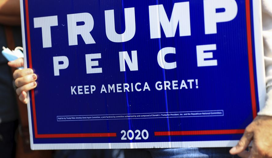 A voter holds a sign in support of Trump, at the Hamilton County Board of Elections as people arrive to participate in early voting, Tuesday, Oct. 6, 2020, in Norwood, Ohio. (AP Photo/Aaron Doster)