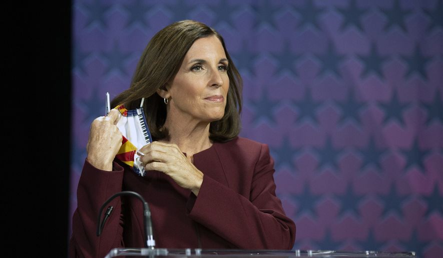 U.S. Sen. Martha McSally, R-Ariz., removes her mask as she prepares to debate Democratic challenger Mark Kelly, Tuesday, Oct. 6, 2020, at the Walter Cronkite School of Journalism at Arizona State University, in Phoenix. (Rob Schumacher/The Arizona Republic via AP, Pool)