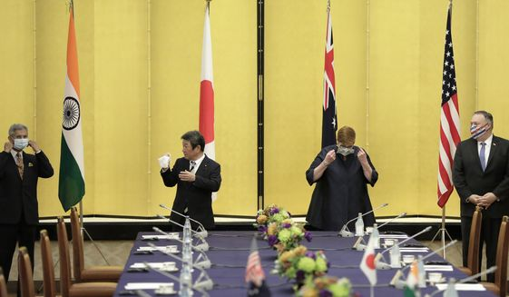 From left; India Foreign Minister Subrahmanyam Jaishankar, Japan Foreign Minister Toshimitsu Motegi, Australia Foreign Minister Marise Payne and U.S. Secretary of State Mike Pompeo remove their protective face masks before posing for a photograph prior to the Quadrilateral Security Dialogue (Quad) ministerial meeting in Tokyo, Tuesday, Oct. 6, 2020. (Kiyoshi Ota/Pool Photo via AP)