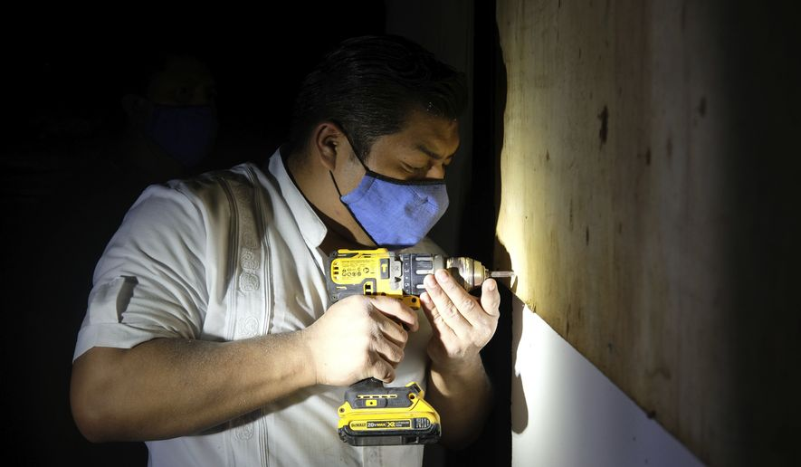 A hotel worker from the Fiesta Americana Condesa resort covers a window with plywood at a shelter set up at the Technological Institute of Cancun, as he prepares for the landfall of Hurricane Delta, in Cancun, Mexico, Tuesday, Oct. 6, 2020. (AP Photo/Luis Henao)