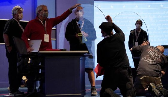 Members of the production crew inspect glass on stage which will serve as a barrier to protect the spread of COVID-19 as preparations take place for the vice presidential debate at the University of Utah, Tuesday, Oct. 6, 2020, in Salt Lake City. The vice presidential debate between Vice President Mike Pence and Democratic vice presidential candidate, Sen. Kamala Harris, D-Calif., is scheduled for Oct. 7. (AP Photo/Julio Cortez)