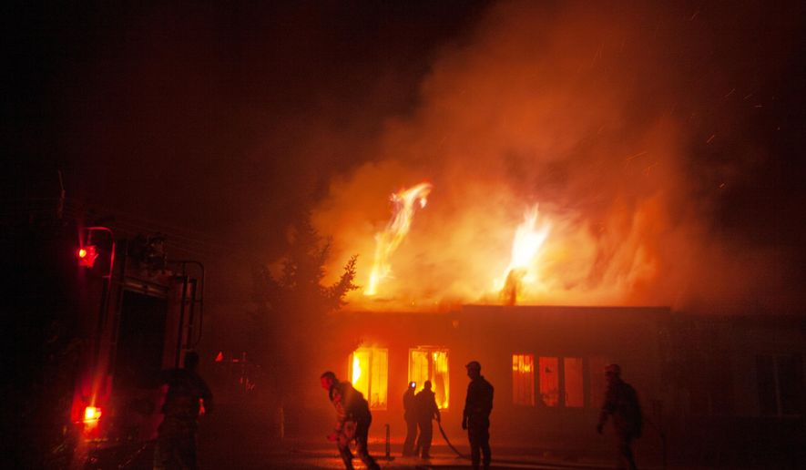 Firefighters work as building of a residential area burns after night shelling in Stepanakert, the self-proclaimed Republic of Nagorno-Karabakh, Azerbaijan, Saturday, Oct. 3, 2020. Heavy fighting between Azerbaijani and Armenian forces in the region since Sept. 27 has killed scores of both servicemen and civilians. Nagorno-Karabakh lies inside Azerbaijan but has been under the control of ethnic Armenian forces backed by Armenia since the 1994. (AP Photo/Karen Mirzoyan)