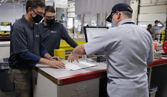 Franklin County Board of Elections employees Seth Golding, left, and Braydon Galliers, center, transfer the chain of custody of blank absentee ballots to Wesley Foust, of the U.S. Postal Service, Monday, Oct. 5, 2020, in Columbus, Ohio. The ballots are being mailed on Tuesday, the first day of early voting for Ohio in the Nov. 3 election. (AP Photo/Jay LaPrete)