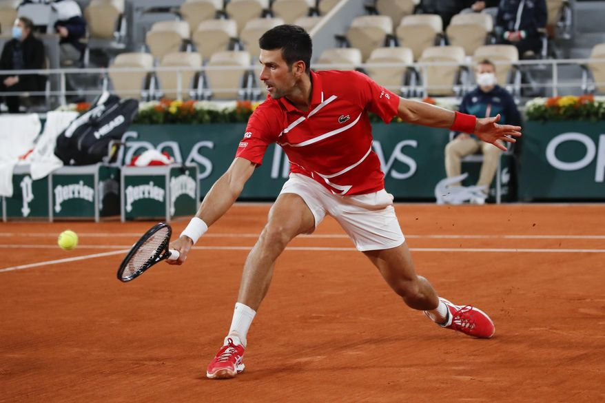 Serbia's Novak Djokovic plays a shot against Russia's Karen Khachanov in the fourth round match of the French Open tennis tournament at the Roland Garros stadium in Paris, France, Monday, Oct. 5, 2020. (AP Photo/Christophe Ena)