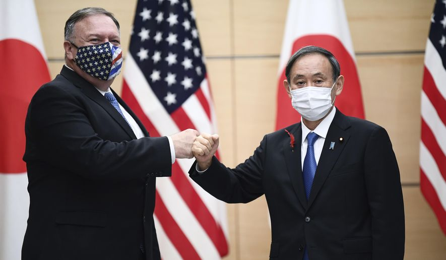 Japan's Prime Minister Yoshihide Suga, right, and U.S. Secretary of State Mike Pompeo, left, greet prior to their meeting at the prime minister's office in Tokyo, Tuesday, Oct. 6, 2020, ahead of the four Indo-Pacific nations' foreign ministers meeting. (Charly Triballeau/Pool Photo via AP) ** FILE **