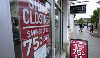 In this Wednesday, Sept. 2, 2020, file photo, passers-by walk past a business storefront with store closing and sale signs in Dedham, Mass. U.S. employers advertised for slightly fewer jobs in August while their hiring ticked up modestly. The Labor Department said Tuesday, Oct. 6, 2020,  that the number of U.S. job postings on the last day of August dipped to 6.49 million, down from 6.70 million July. (AP Photo/Steven Senne, File)