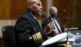 FILE - In this Sept. 9, 2020 file photo Surgeon General Jerome Adams, appears before a Senate Health, Education, Labor and Pensions Committee hearing on Capitol Hill, in Washington. Adams was cited for being in a closed Hawaii park in August while in the islands helping with surge testing amid a spike in coronavirus cases, according to a criminal complaint filed in court. (Michael Reynolds/Pool via AP,File)