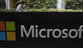 FILE - A man wearing a mask looks at this phone outside the Microsoft office in Beijing, China in a Friday, Aug. 7, 2020 file photo. Microsoft says the U.S. Labor Department is investigating its efforts to boost Black employment and leadership at the tech company. Microsoft disclosed in a blog post Tuesday, Oct. 6, 2020 that it received a letter from the agency last week asking about the company's June pledge to double the number of Black and African American people managers, senior individual contributors and senior leaders by 2025. (AP Photo/Ng Han Guan, File)