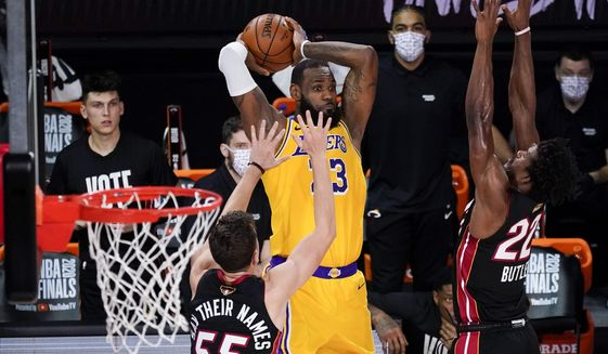 Los Angeles Lakers forward LeBron James passes between Miami Heat guard Duncan Robinson, left, and forward Jimmy Butler during the second half in Game 4 of basketball's NBA Finals Tuesday, Oct. 6, 2020, in Lake Buena Vista, Fla. (AP Photo/John Raoux)