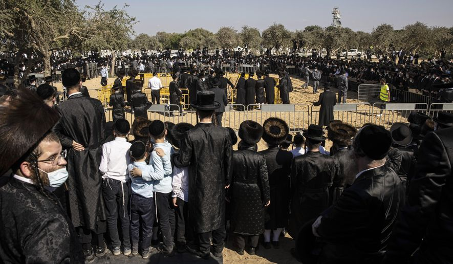 Large numbers of ultra-Orthodox Jews gather for the funeral for Rabbi Mordechai Leifer, in the port city of Ashdod, Israel, Monday, Oct. 5, 2020. After a revered ultra-Orthodox rabbi died this week, Israeli police thought they had worked out an arrangement with his followers to allow a small but dignified funeral that would conform with public health guidelines under the current coronavirus lockdown. The repeated violations by segments of the ultra-Orthodox population have confounded public health experts and tested Prime Minister Benjamin Netanyahu's longstanding political alliance with religious leaders. (AP Photo/Tsafrir Abayov)